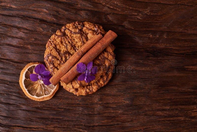 Chocoladekoekjes dichtbij bloem op de achtergrond van eik Het gezonde concept van het ochtendontbijt De minimalistische vlakte va stock fotografie