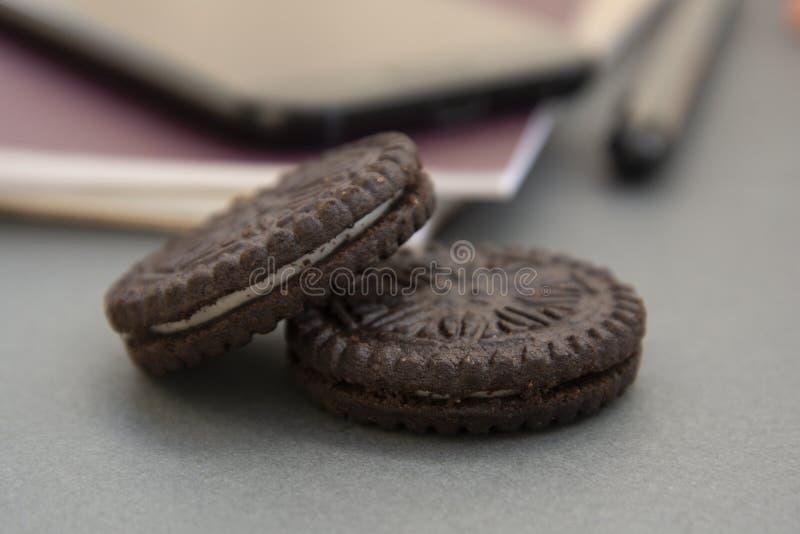 Chocoladekoekjes op het werklijst, zoete snack op het werk stock fotografie