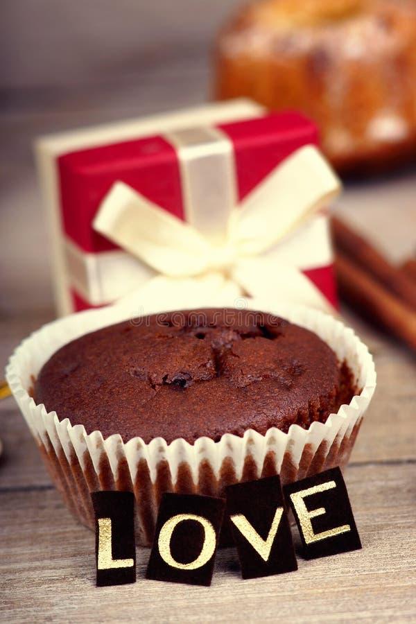 Chocolademuffin, giftdoos en woordliefde royalty-vrije stock fotografie