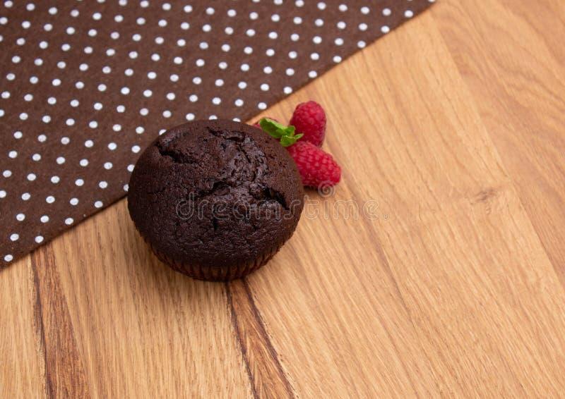 Chocolademuffin met frambozenbessen op een lichte houten lijst stock foto