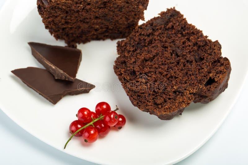 Chocolademuffin met rode aalbes op plaat op witte achtergrond Het dessert van het chocoladebaksel stock foto's