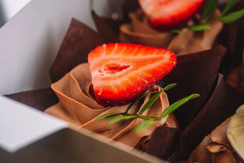 Chocolademuffins met aardbeien en room Chocolademuffins met aardbeien en room stock fotografie
