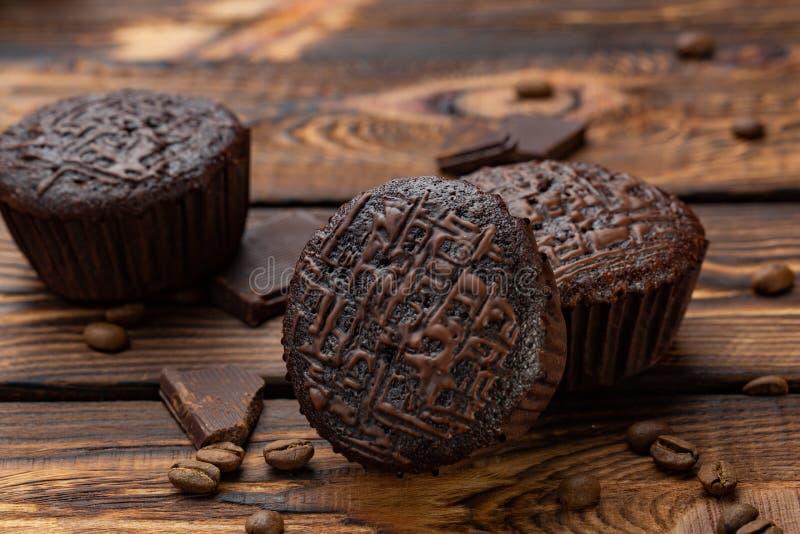 Chocolademuffins op een broun rustieke houten lijst - selectieve nadruk stock fotografie