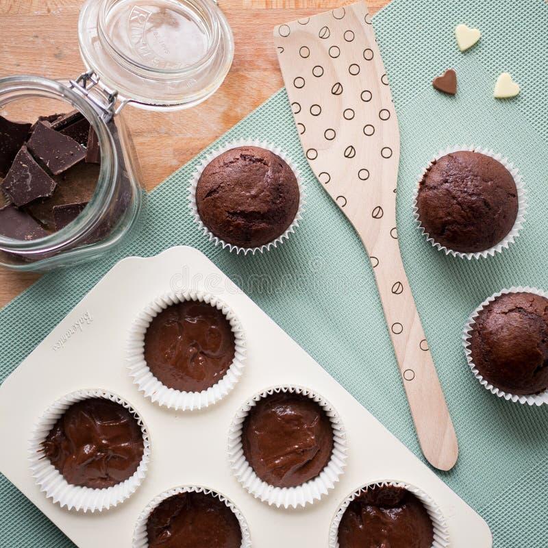 Chocolademuffins op een houten lijst met keukengereedschap, een kruikhoogtepunt van chocoladestukken en haard-vormige chocolade royalty-vrije stock foto