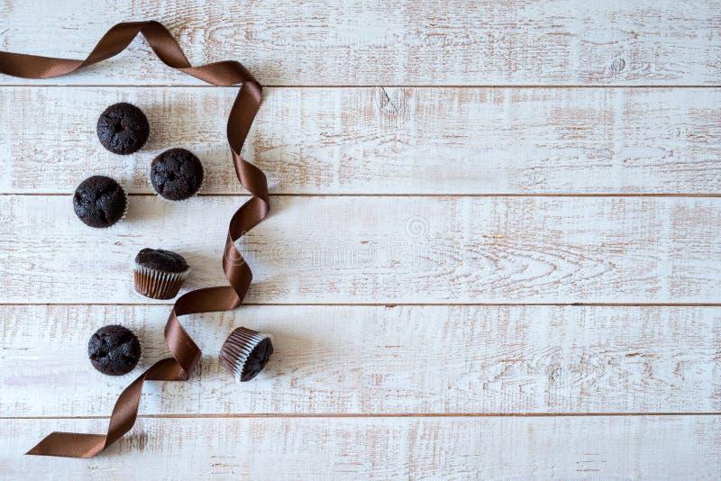 Chocolademuffins op een witte rustieke houten lijst stock afbeeldingen