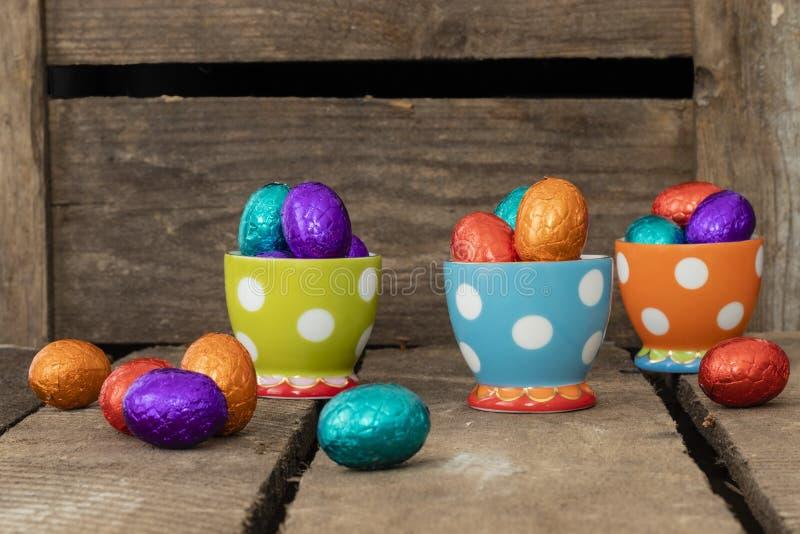 Chocoladepaaseieren in drie kleurrijke eierdopjes stock foto's
