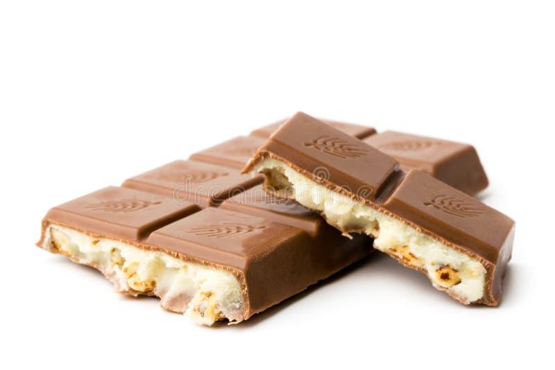 Chocoladereep met condens en noten op een witte achtergrond worden gebroken die stock fotografie