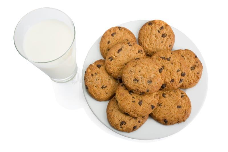 Chocoladeschilferkoekjes en een glas melk stock afbeelding