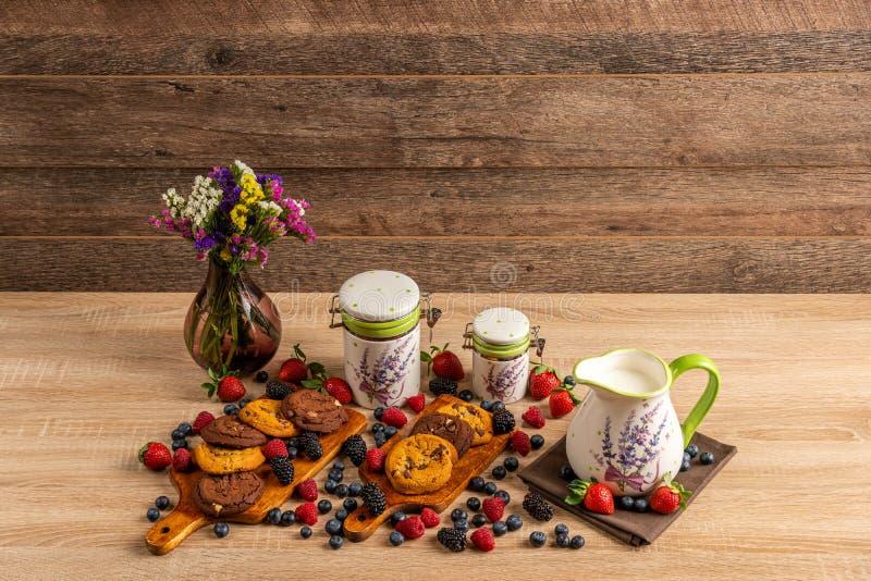 Chocoladeschilferkoekjes met melk in ceramische kruik en mengeling van bosvruchten stock afbeeldingen