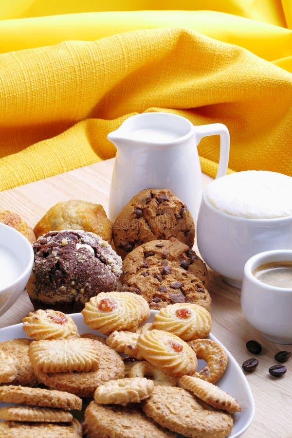 Chocoladeschilferkoekjes, muffins, kleine gebakjes met koffie en melk stock afbeelding
