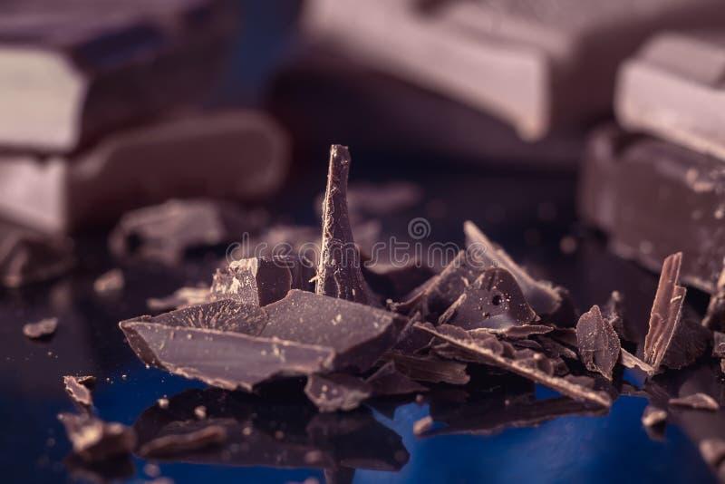 Chocoladeschilfers en stukken van donker bittere chocoladeclose-up, macroschot stock afbeelding