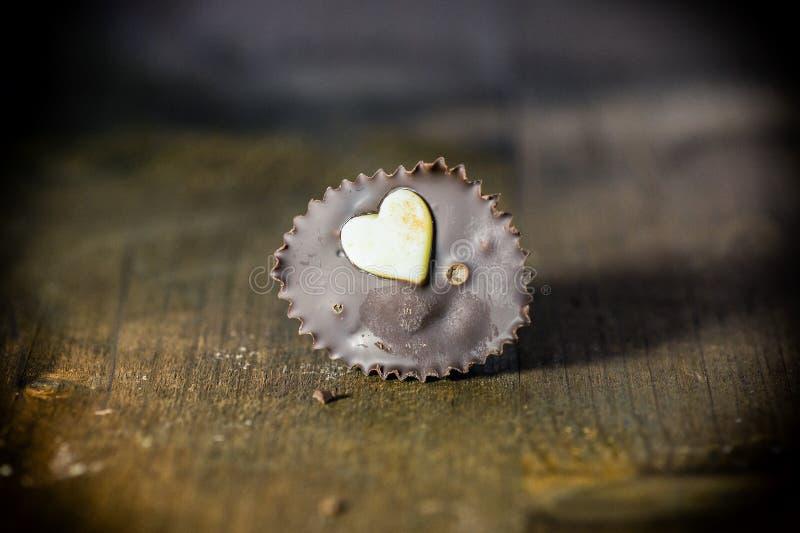 Chocoladesuikergoed met hart Houten achtergrond stock afbeeldingen