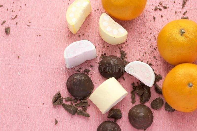 Chocoladesuikergoed met sinaasappel en heemst Snoepjes, citrusvrucht, desserts op roze achtergrond met exemplaarruimte stock foto