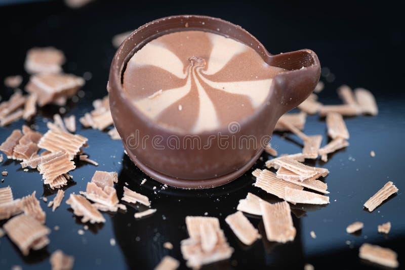 Chocoladevlokken op een zwarte plaat met een praline stock foto