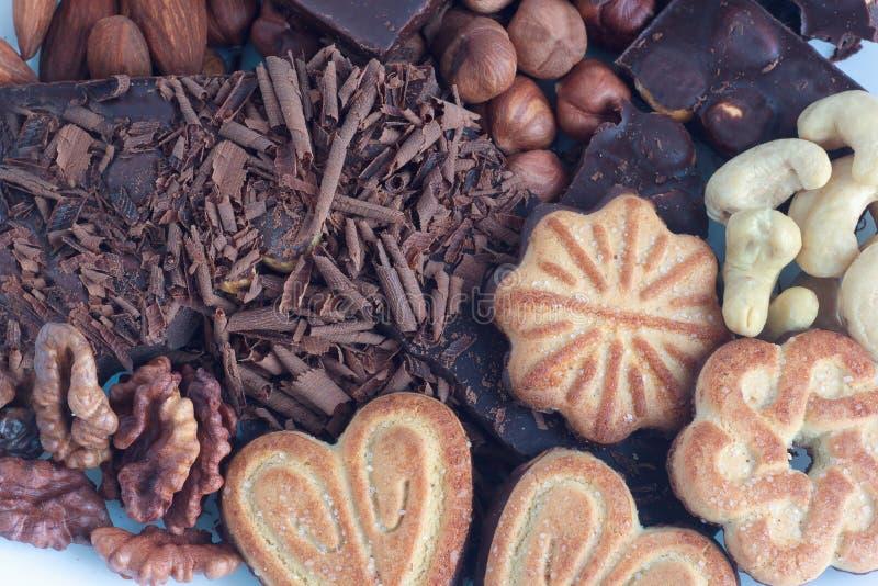 Chocolat, biscuits et écrous se trouvant sur la table de dîner photo libre de droits
