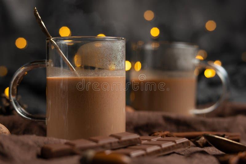 Chocolat chaud d'hiver riche avec les bâtons de cannelle et les noix, barres de chocolat dans une tasse transparente sur un panne photos libres de droits