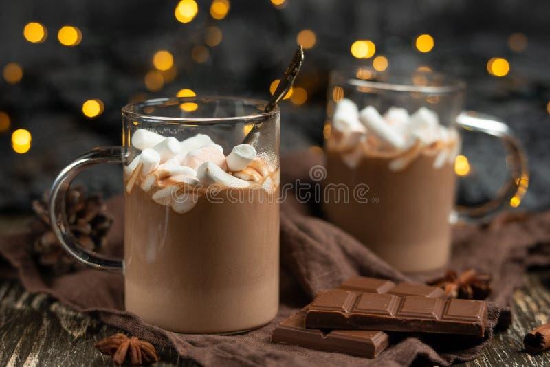 Chocolat chaud d'hiver riche avec les bâtons de cannelle et les noix, barres de chocolat dans une tasse transparente sur un panne photographie stock libre de droits