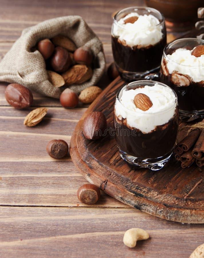 Chocolat chaud en tasses et crème en verre avec des écrous images stock