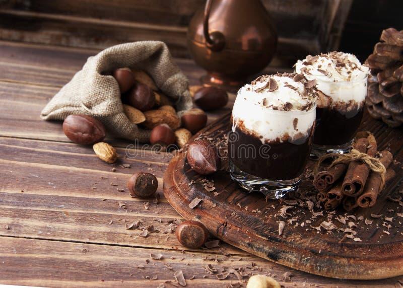 Chocolat chaud en tasses et crème en verre avec des écrous photographie stock libre de droits