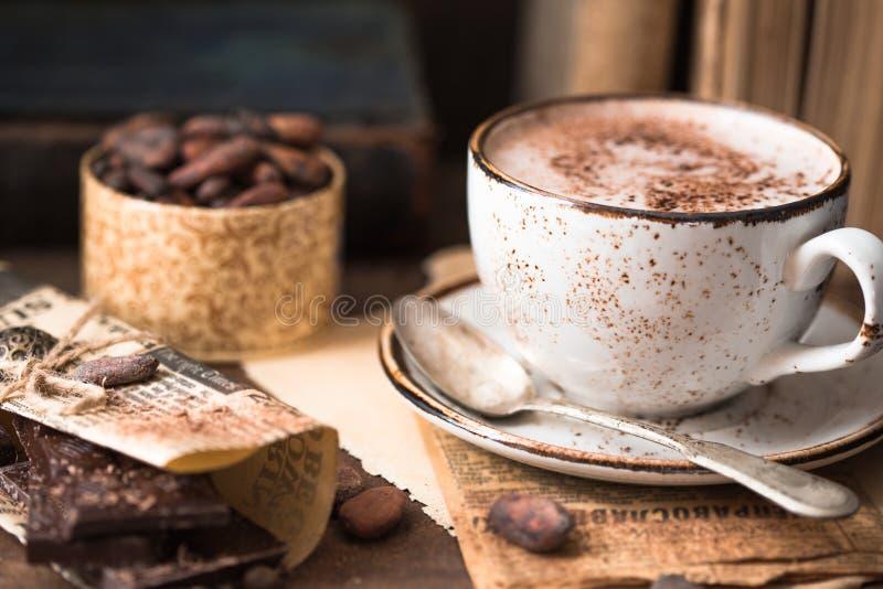 Chocolat chaud et morceaux de chocolat au-dessus de fond en bois rustique Boisson faite maison de chocolat chaud pendant des vaca image stock