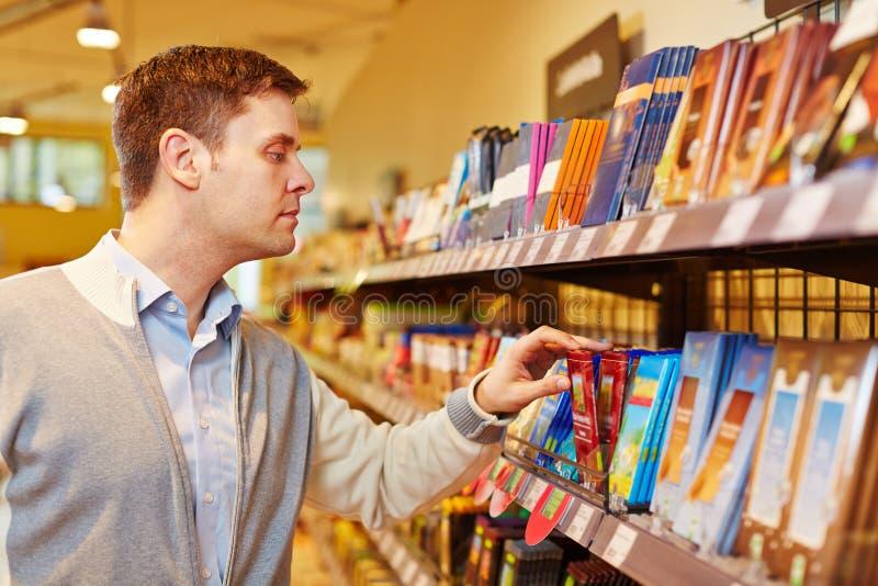 Chocolat de achat d'homme dans le supermarché photo stock
