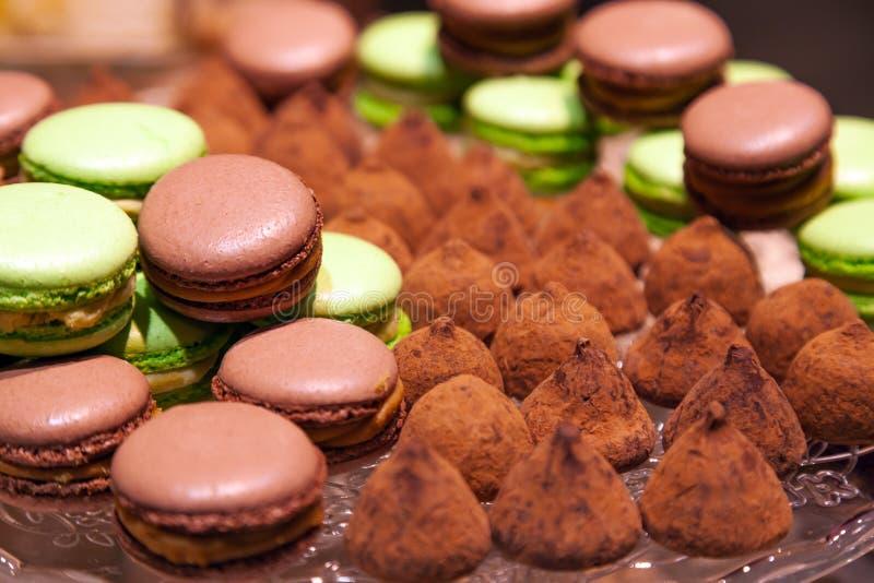 Chocolat de plan rapproché et macarons et truffes de pistache arrosés avec du cacao dans un plat en cristal Vue de ci-avant Table photographie stock