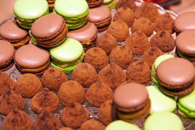 Chocolat de plan rapproché et macarons et truffes de pistache arrosés avec du cacao dans un plat en cristal Vue de ci-avant Table images stock