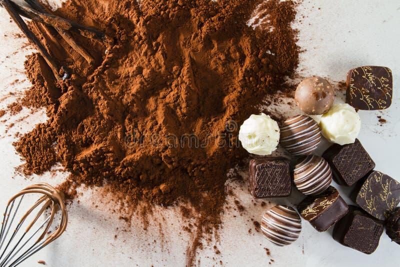 CHOCOLAT DE PRALINE EN POUDRE DE CACAO CHOCOLAT FAIT MAISON DANS LE TRAVAIL AVEC LE BATTEUR ET LA GOUSSE DE VANILLE D'OEUFS SUR L photo libre de droits