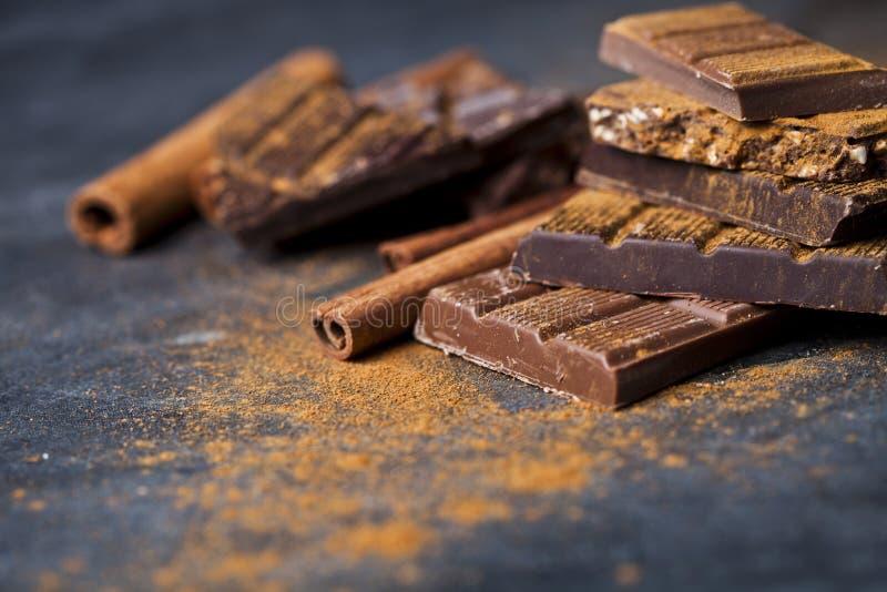 Chocolat empil? sur le fond noir Les morceaux de barre de chocolat amassent la poudre et les b?tons de cannelle de witn images stock