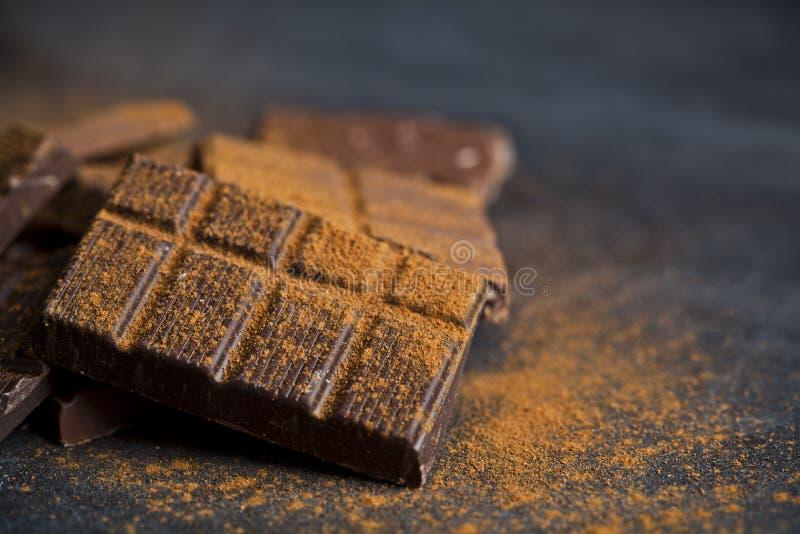 Chocolat empil? sur le fond noir Les morceaux de barre de chocolat amassent la poudre de cannelle de witn photographie stock libre de droits