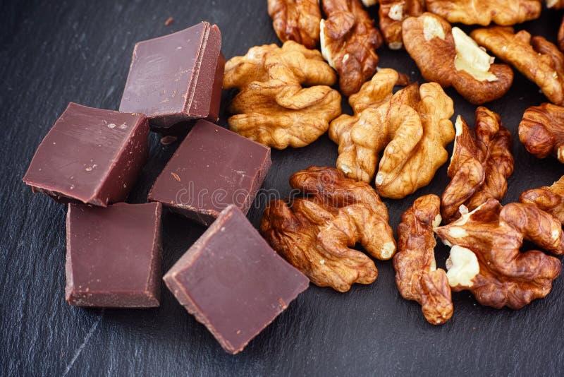 Chocolat noir cassé et noix brutes bio images libres de droits