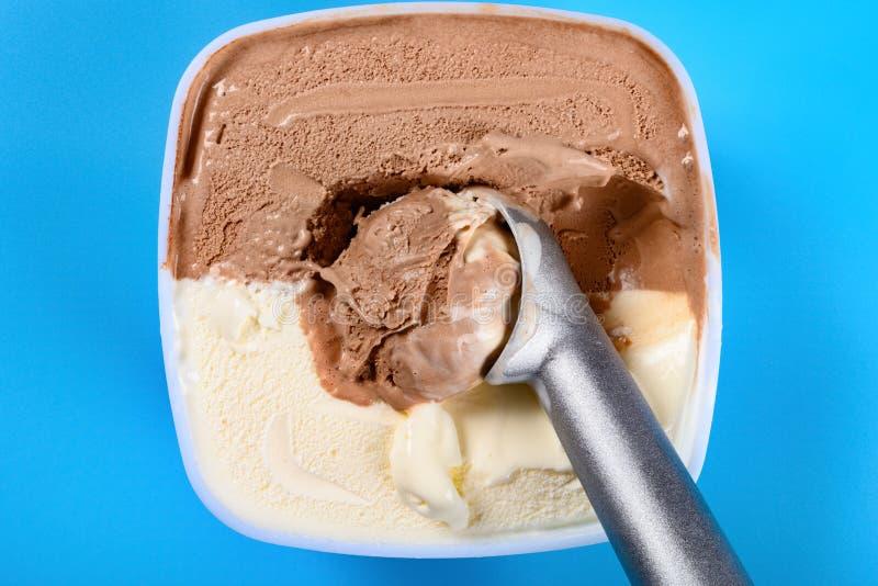 Chocolat plus la glace à la vanille avec une cuillère et certains digged sur le fond bleu images libres de droits