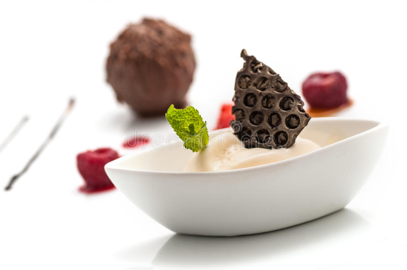 Chocolate ball with ice cream and fruit on white plate, sweet dessert with chocolate, product photography for patisserie or restau stock image