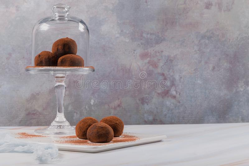 Chocolate balls cakes in a glass stand. Cocoa balls, chocolate balls cakes in a glass stand, sprinkled with cocoa powder royalty free stock image