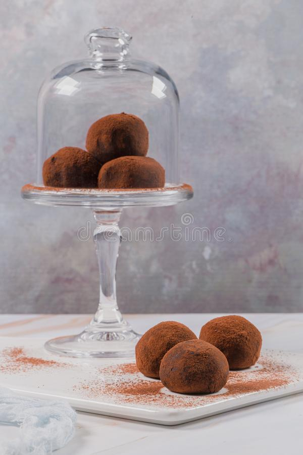 Chocolate balls cakes in a glass stand. Cocoa balls, chocolate balls cakes in a glass stand, sprinkled with cocoa powder stock photos