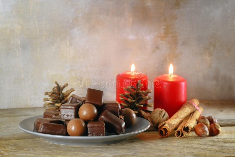 Chocolate balls and gingerbread cookies, in germany called dominosteine, red candles and decoration for Advent and Christmas on a. Rustic wooden table, copy royalty free stock image