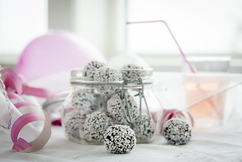 Chocolate balls in glass jar. Kids birtday party with chocolate balls in glass jar and a pink balloon stock images
