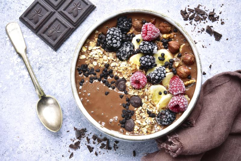 Chocolate banana smoothie bowl with frozen berries and granola.T stock photography