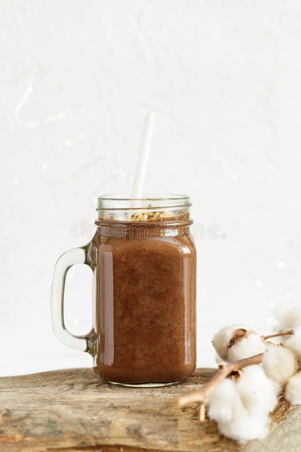 Chocolate banana smoothie on a rustic table. Warm winter season beverage stock photo