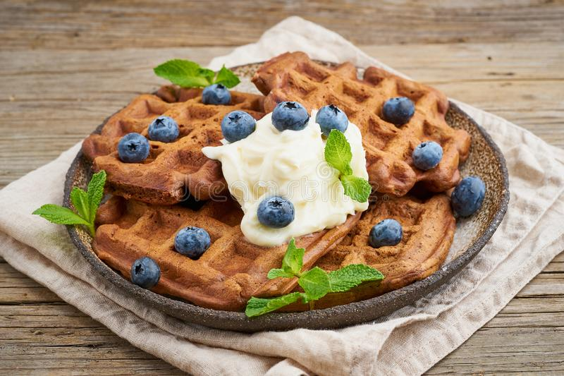 Chocolate banana waffles with blueberries, on dark wooden old table. Side view. Chocolate banana waffles with blueberries, on dark wooden the old table. Side royalty free stock photo