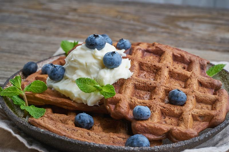 Chocolate banana waffles with blueberries, on dark wooden old table. Side view, close up. Chocolate banana waffles with blueberries, on dark wooden the old table stock photos