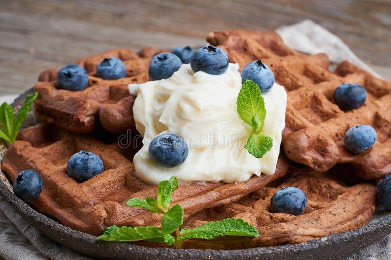 Chocolate banana waffles with blueberries, on dark wooden old table. Side view, close up. Chocolate banana waffles with blueberries, on dark wooden the old table stock images