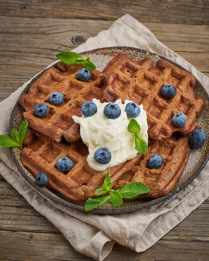 Chocolate banana waffles with blueberries, on dark wooden old table. Side view, vertical. Chocolate banana waffles with blueberries, on dark wooden the old table stock photography
