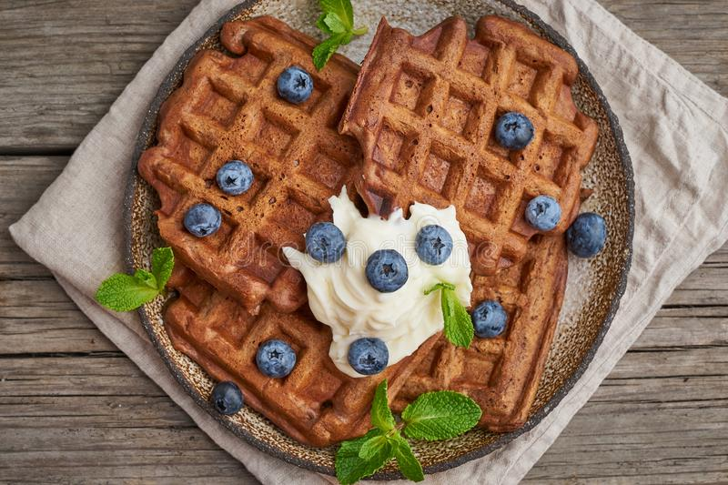 Chocolate banana waffles with blueberries, on dark wooden old table. Top view, close up. Chocolate banana waffles with blueberries, on dark wooden the old table royalty free stock photo