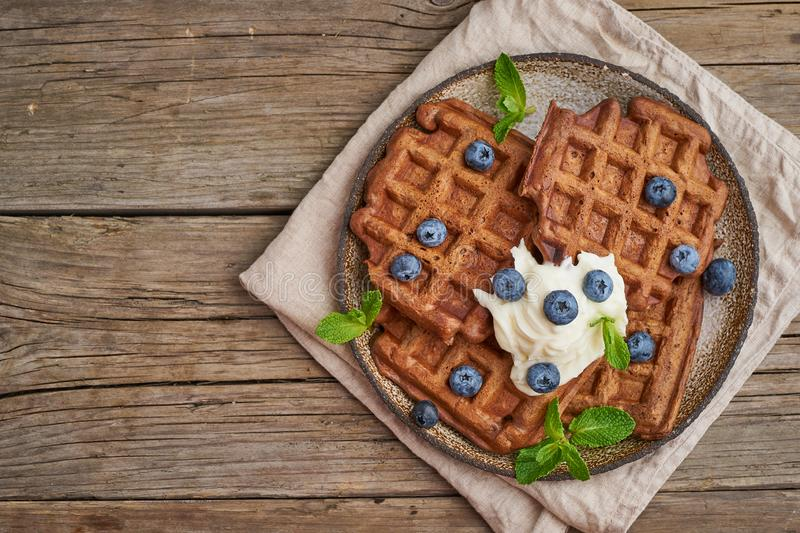 Chocolate banana waffles with blueberries, on dark wooden old table. Top view, copy space royalty free stock photo