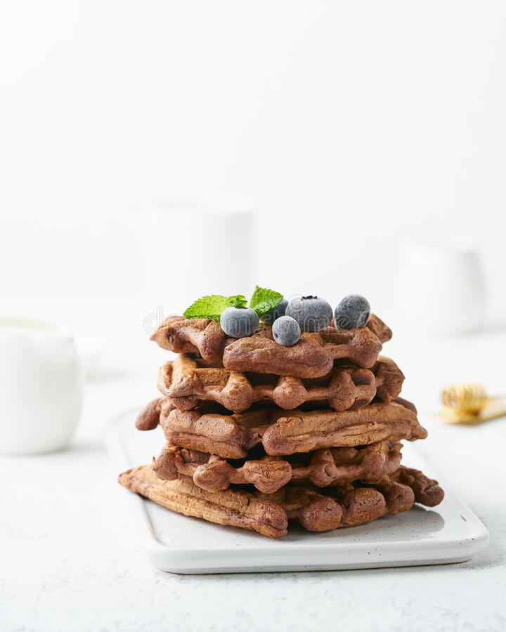 Chocolate banana waffles with blueberry on white table. Side view, vertical. Chocolate banana waffles with blueberry on a white table. Side view, vertical stock photos