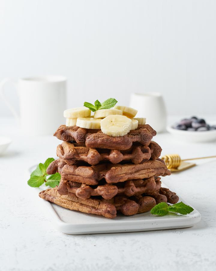 Chocolate banana waffles with maple syrup on white table, side view, vertical. Sweet brunch. Chocolate banana waffles with maple syrup on a white table, side stock photography