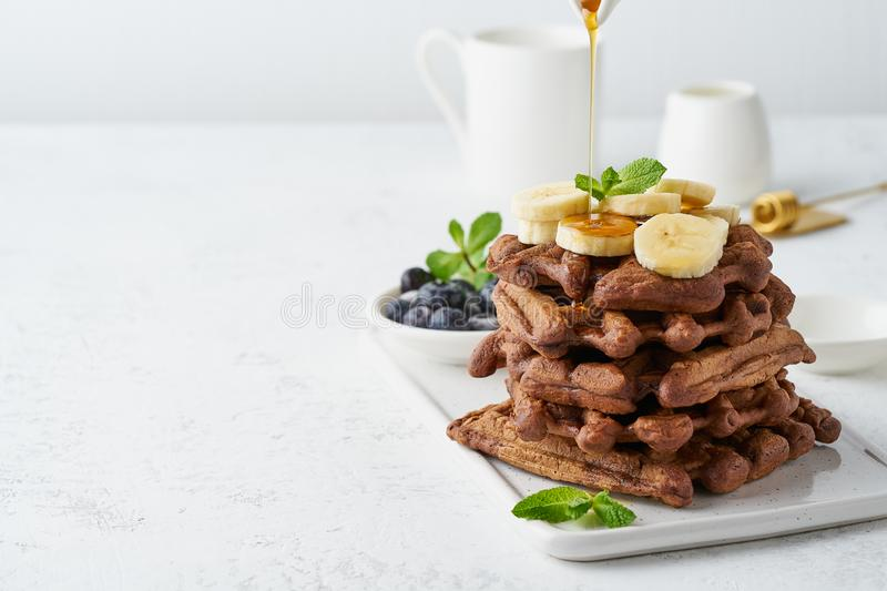 Chocolate banana waffles on white table, copy space, side view. Sweet brunch, maple syrup flow stock image