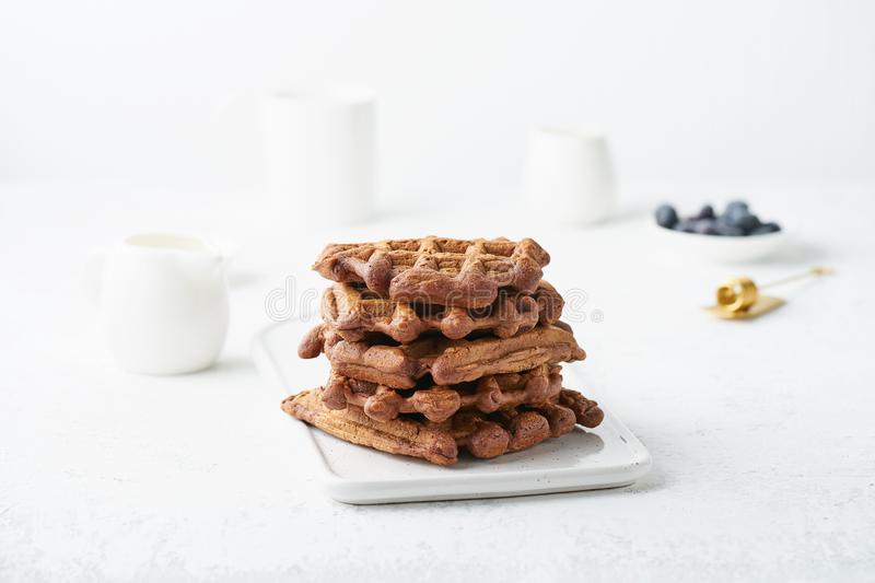 Chocolate banana waffles on white table. Scandinavian minimalist style, side view. Chocolate banana waffles on a white table. Scandinavian minimalist style, side royalty free stock photography