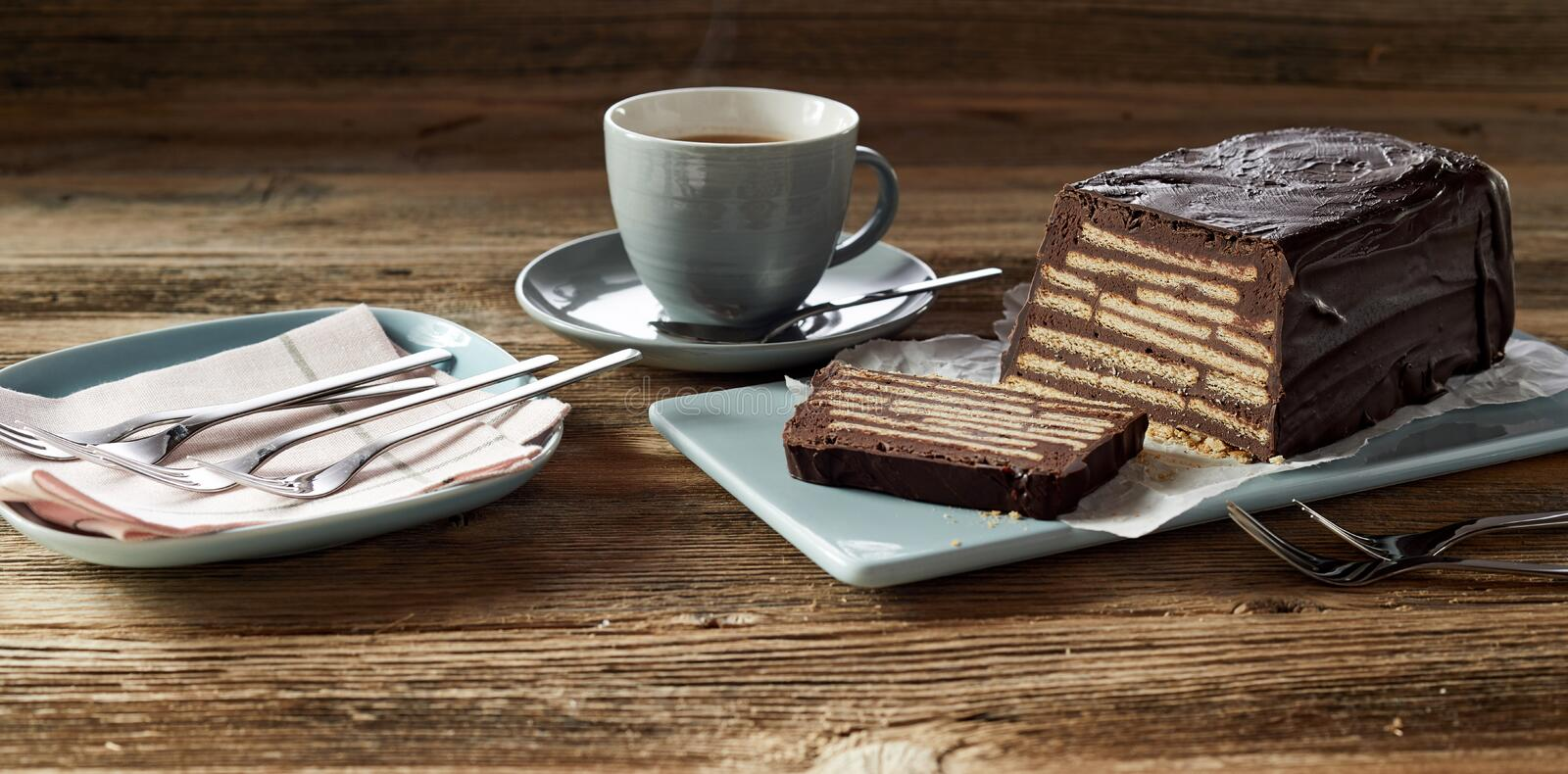 Chocolate bar cake with coffee. Chocolate bar cake Kalter Hund, served with coffee and forks on blue ceramic plate on rustic unpainted wooden table surface stock photo